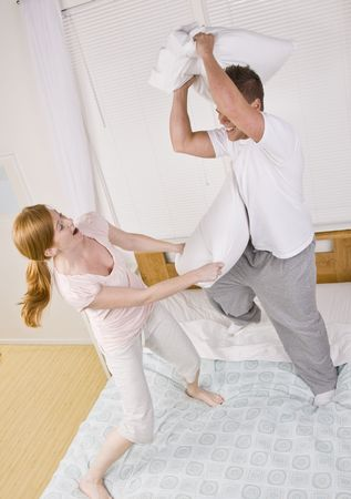 An attractive young couple having a pillow fight in their pajamas.  They are standing on a bed and are smiling. Vertically framed photo. photo