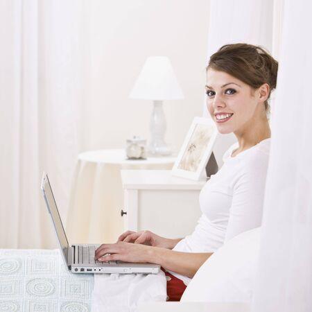 Une jolie jeune femme couch�e dans son lit et l'utilisation d'un ordinateur portable. Elle est souriant � la cam�ra. Square photo encadr�e. Banque d'images - 5120719
