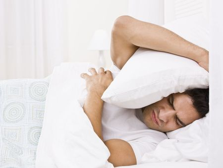 cushion: A tired looking man in bed.  He is holding a pillow over his head and is scowling. Horizontally framed shot. Stock Photo