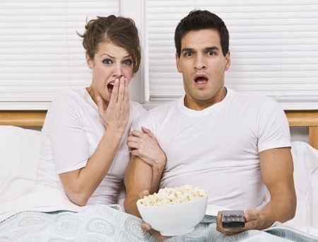 they are watching: A young, attractive couple is sitting together in bed and watching TV.  They look shocked or scared, and are looking away from the camera.  Horizontally framed shot.