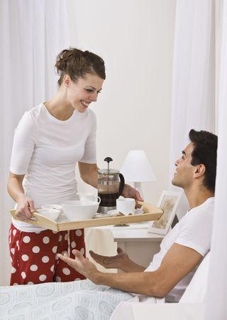 Attractive woman serving breakfast in bed. vertical