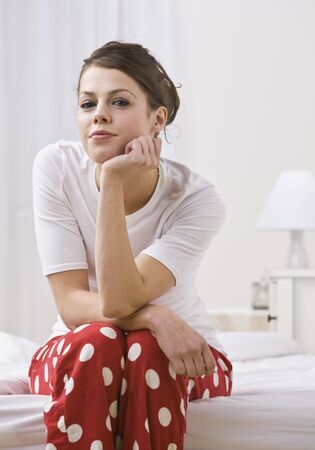 An attractive young woman sitting on the edge of a bed in her pajamas.  She is resting her chin on her hand and is smiling slightly toward the camera. Vertically framed photo. photo