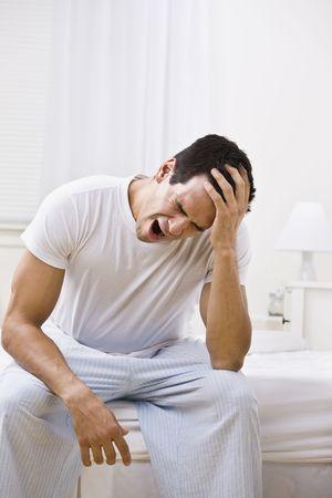 Een man geeuwen. Hij zit op de rand van een bed. Verticaal framed shot. Stockfoto