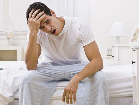 Un hombre enorme. Él está sentado en el borde de una cama está tocando su frente. Foto enmarcada horizontalmente.