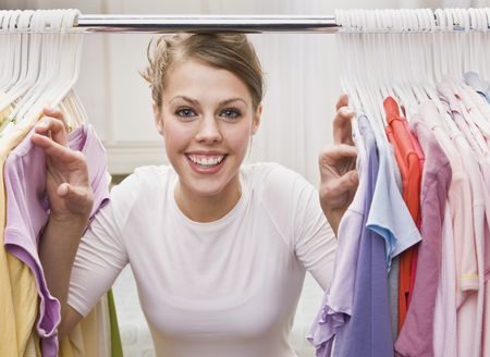 closet: A young, attractive woman is standing in a closet and looking through clothes.  She is smiling at the camera.  Horizontally framed shot.
