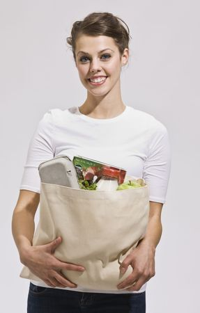 Attractive woman with grocery bag in arms. vertical Reklamní fotografie