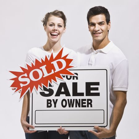 An attractive young couple holding a real estate sign with a sold sticker on it.  They are smiling directly at the camera and look excited. Square. photo