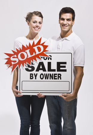 A young couple holding a real estate sign that reads sold. They are smiling and are facing the camera. Vertically framed photo. photo