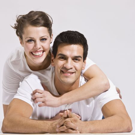 east asian ethnicity: An attractive couple posing for a photo.  The female has her arm embraced around the males neck.  They are both smiling. Square framed photo.