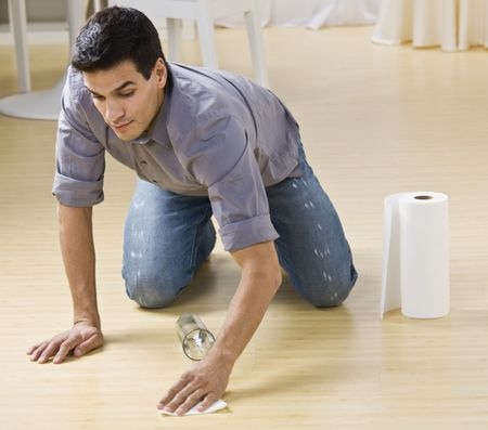 A man cleaning up a spilled glass of water.  He is using paper towels on a wood floor. Horizontally framed photo. Archivio Fotografico