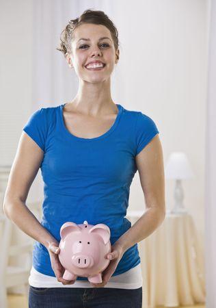 Beautiful woman holding piggy bank. Vertically framed shot. Stock Photo - 5120619