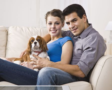 midlife: An attractive young couple sitting on a couch together and holding a dog. They are smiling and looking directly at the camera. Horizontally framed photo.