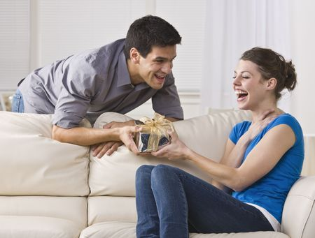 Man giving laughing woman gift. horizontal photo