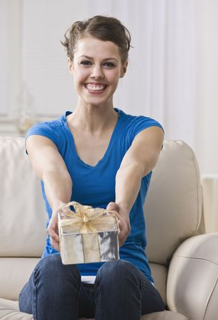 An attractive young woman sitting on a couch and presenting a gift box.  She is smiling at the camera. Vertically framed photo. photo