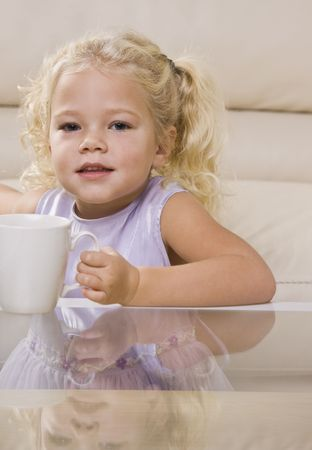A young girl is sitting at the coffee table and drinking out of a mug.  She is looking at the camera.  Vertically framed shot. photo