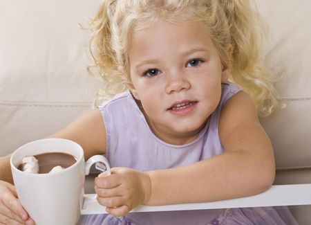 A young girl is sitting at the coffee table and drinking out hot chocolate and marshmallows out of a mug.  She is looking at the camera.  Vertically framed shot. photo