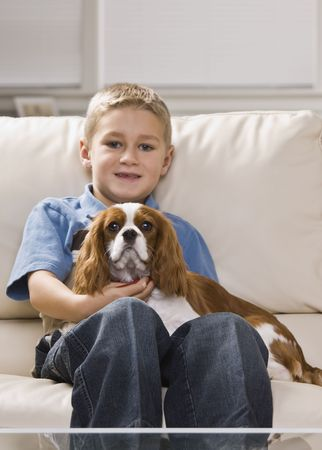 white sofa: A cute little boy holding a dog on his lap.  He is smiling.  Vertically framed shot.