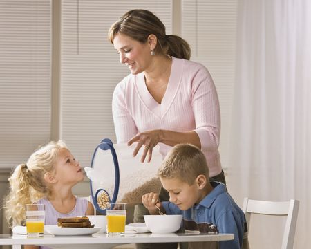 A beautiful family eating breakfast together. The mother is smiling and is pouring cereal for the daughter.  Horizontally framed shot.