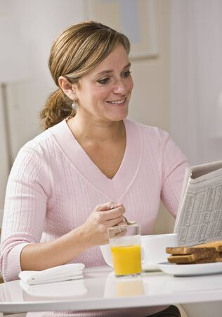 midlife: A young woman is eating breakfast and reading a newspaper.  She is smilign at the camera.  Vertically framed shot.