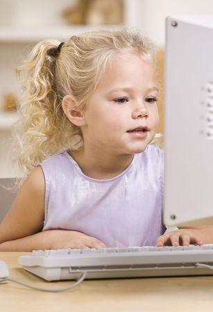 vertically: A beautiful little girl using a computer.  Vertically framed shot.