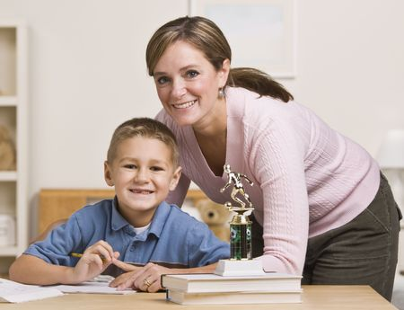 midlife: A mother is helping her  young son with his homework.  They are both smiling at the camera.  Horizontally framed shot.