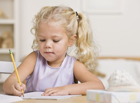 scribbling: A young girl is writing in a notebook.  She is looking away from the camera.  Horizontally framed shot.