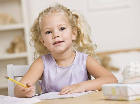 A young girl is sitting at a table and coloring in books.  She is looking at the camera.  Horizontally framed shot. photo