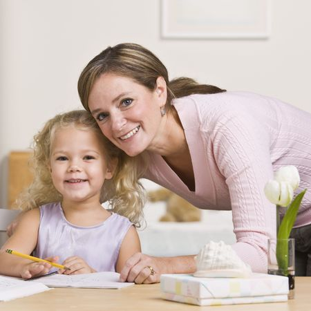 A mother is sitting with her young daughter and watching her draw.  They are smiling at the camera.  Square framed shot. Stock Photo