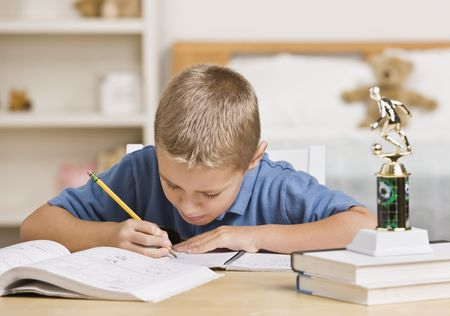 A young boy is working on his homework at the table.  He is looking away from the camera.  Horizontally framed shot. Stock Photo - 5333543
