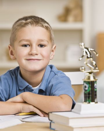 A young boy is seated at a desk with a stack of books and a trophy.  He is smiling at the camera.  Vertically framed shot. Stock Photo - 5333528