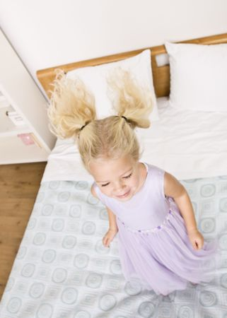 A young girl is jumping up and down on a bed.  She is smiling and looking away from the camera.  Vertically framed shot. photo