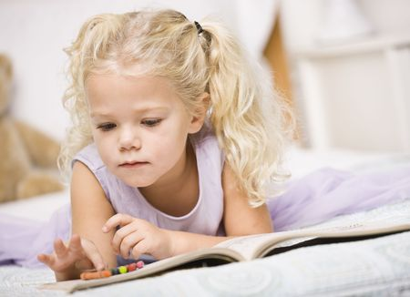 A young girl is laying on a bed and coloring in books.  She is looking away from the camera.  Horizontally framed shot. photo