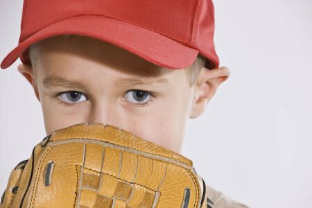 A young boy is wearing a baseball cap and holding a baseball mitt up to his face.  Horizontally framed shot. photo