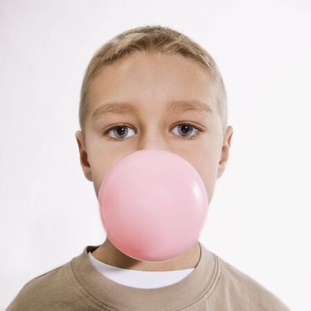 A young boy is chewing bubble gum and blowing a bubble.  He is looking at the camera.  Vertically framed shot.