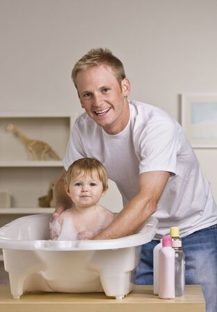 A young father is giving his baby daughter a bath in a childs bathtub.  He is smiling at the camera.  Vertically framed shot. Stock Photo - 5333435