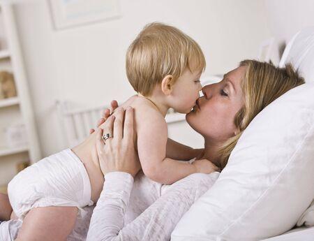 people kissing: Une belle jeune m�re embrasser son b�b�.  Shot horizontalement encadr�s.