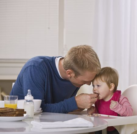 A young father feeding his daughter cereal at a breakfast table.  They are looking away from the camera. Square framed shot. photo
