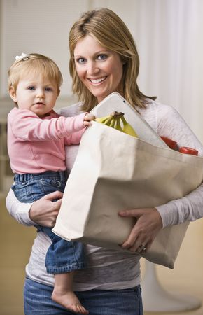 A young mother is holding her daughter in one arm and a bag of groceries in the other.  She is smiling at the camera.  Vertically framed shot.