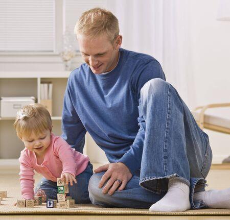 padre e hija: Un padre joven est� en el piso que jugando con su hija.  �l es sonriente y mirando de ella.  Cuadrado disparo enmarcado. Foto de archivo