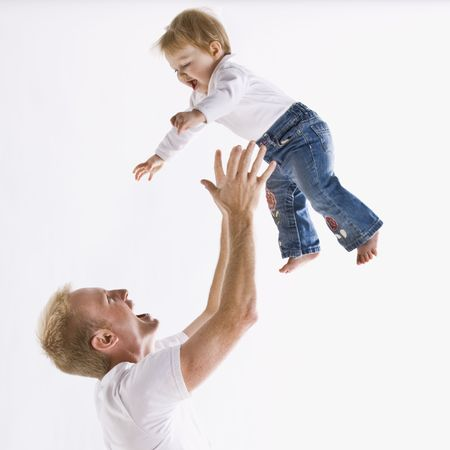 A young father is playing with his daughter and throwing her up in the air.  They are smiling at each other.  Square framed shot.