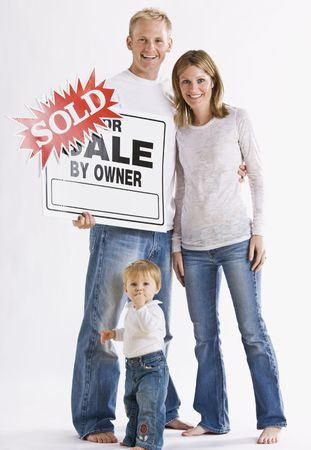 A young family is standing in front of a For Sale Sign and are smiling at the camera.  Vertically framed shot. Stock Photo - 5333208