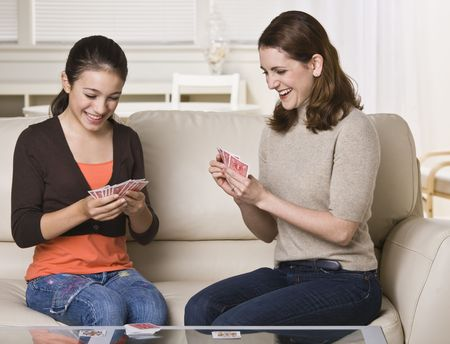 A mother and her daughter are seated on the living room sofa and are playing cards together.  They are smiling and looking away from the camera.  Horizontally framed shot. photo