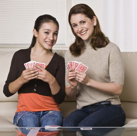 A young mother and her daughter are playing cards together.  They are smiling at the camera.  Square framed shot. photo