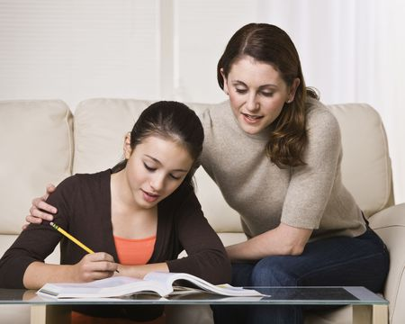 A mother is helping her young daughter with her homework.  They are looking away from the camera.  Horizontally framed shot. photo