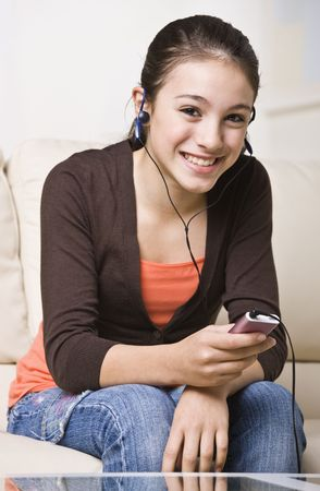 A happy young teenager listening to an MP3 music player.  She is smiling at the camera.  Vertically framed shot.