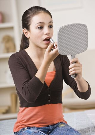 teen girl bedroom: A young girl is looking into a hand mirror and putting makeup on.  Vertically framed shot.
