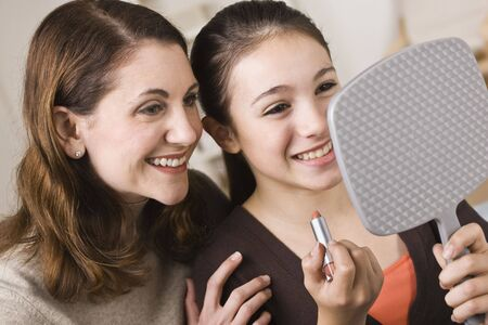 A beautiful young girl holding a mirror and a tube of lipstick with her mother.  They are smiling.  Horizontally framed shot. photo