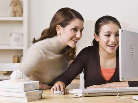A mother and her teenage daughter are looking at a computer together.  Horizontally framed shot.