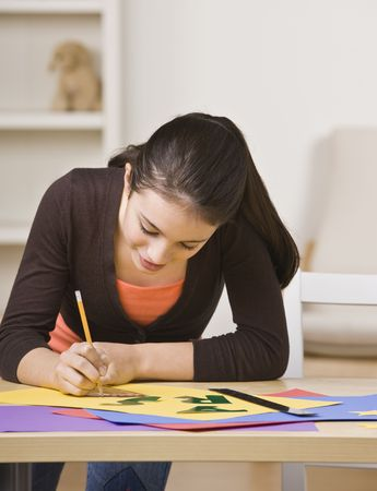 A young girl is working on a project.  She is smiling and looking down at her work.  Square framed shot. Stock Photo - 5333814
