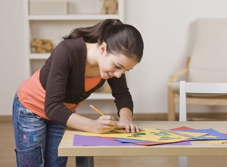 A young girl is working on a project.  She is smiling and looking down at her work.  Square framed shot. Stock Photo - 5333426